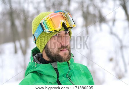 Portrait of a handsome man with a beard and a protective mask. Man in bright winter jacket and hat winter extreme.