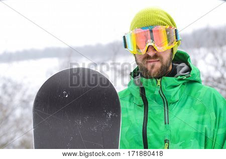 Young Man Standing In The Snow Of A Snowboard And In A Protective Mask On His Face.