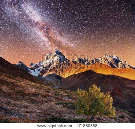 Fantastic collage. Starry sky above snow-capped mountain peaks. Autumn landscape. Main Caucasian Ridge. Georgia. Europe