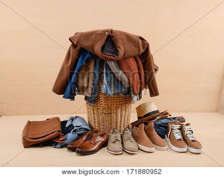 Laundry in a wicker basket and men's shoes, clothes jeans-wooden background