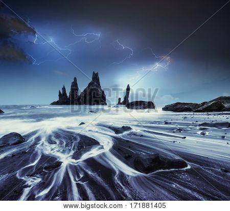 Lightning in cloudy dark sky. Annual Fantastic night scene. The Rock Troll toes. Reynisdranhar rock. Black Sand Beach. Iceland.