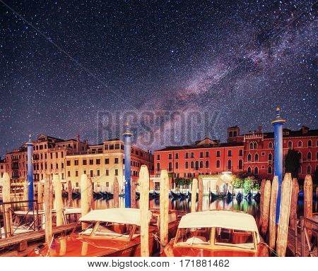 City landscape. Fantastic starry sky and the milky way. The water from boats and gondolas in the background. The colorful facades of old medieval buildings. Venice. Italy. Europe