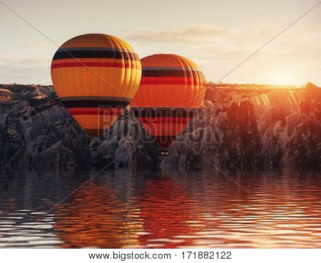Composition of balloons over water and valleys, gorges, hills, between the volcanic mountains at sunset. Cappadocia, Turkey