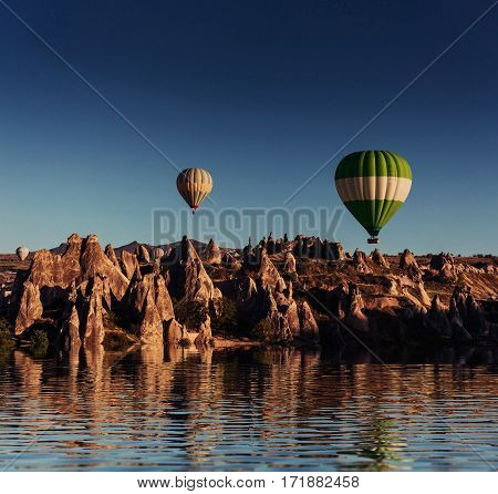 Composition of balloons over water and valleys, gorges, hills, between the volcanic mountains. Cappadocia, Turkey