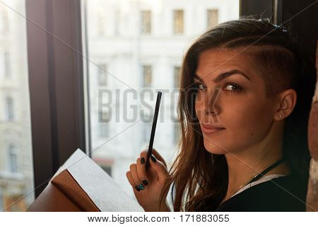 Attractive latin girl on windowsill with notebook and pencil. Woman write notes near window. Brightenning effect. Idoor view to the street.