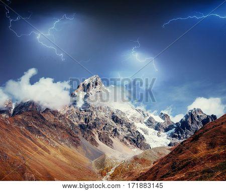 Fantastic collage. Beautiful lightning over the snow-capped mountain peaks. Autumn landscape. Main Caucasian Ridge. Georgia. Europe. Art photography