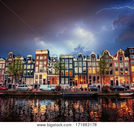 Amsterdam canal at beautiful cumulus clouds and lightning. The city is the capital and most populous city in the Netherlands