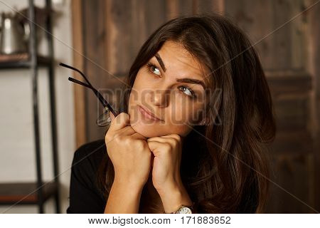 High detailed close up portrait of pretty latin girl in modern loft interior with metall stillage with wooden shelves. Big wood door background. Thinking or dreaming emotion.