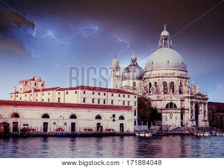 Fantastic views of the Grand Canal and the Basilica Santa Maria della Salute. Lightning strike on the cloudy dark sky. Italy. Venice, Italy. Europe