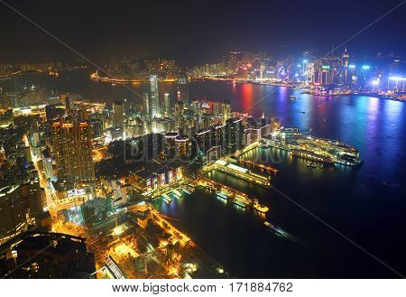 Hong Kong at night. Aerial view of Victoria Harbour and Hong Kong Central. Taken from skyscraper