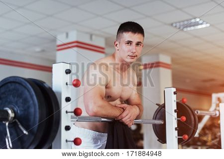 Beautiful man with big muscles, posing for the camera in a nice bright room gym. Sport. Fitness