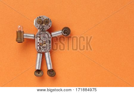 Mechanical cogs wheels character made of clockwork gears and elements. Funny abstract toy with light lamp bulb on orange textured paper background. Up view closeup
