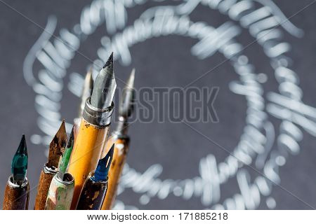 Retro style fountain pen set, abstract letters gray background. macro view, shallow depth of field photo
