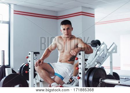 Portrait of a handsome man doing exercises in the gym with a naked torso