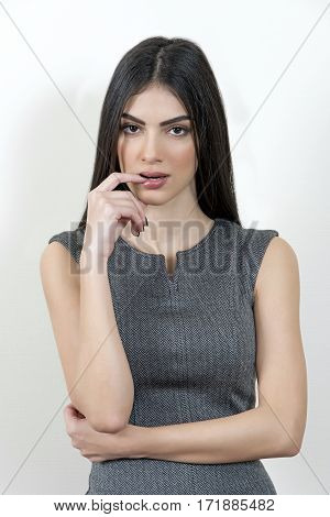 Young business woman looking at the camera with her finger close to her mouth.