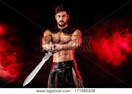 Portrait of handsome muscular gladiator with sword. Studio shot. Black background.