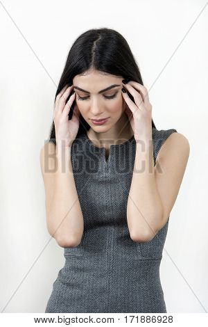 Young business woman has her hands on her face and looking down.