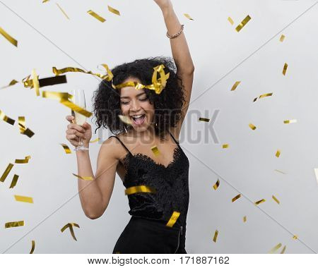Happy woman dancing under confetti with glass of champagne at party