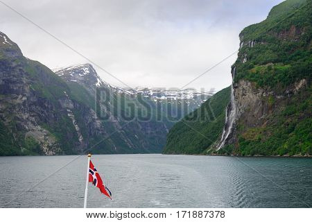 Seven Sisters waterfall falling of the mountain seen from a car ferry ship with a Norwegian flag on the Geirangerfjord from Hellesylt to Geiranger in Norway.