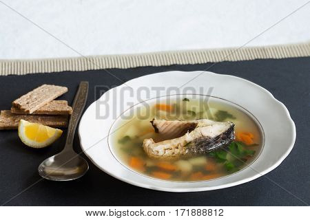 Fish soup on black stone background. Vintage white plate with sliced fish, potato, carrot and herbs. slice lemon, aged spoon, bread. Up view.
