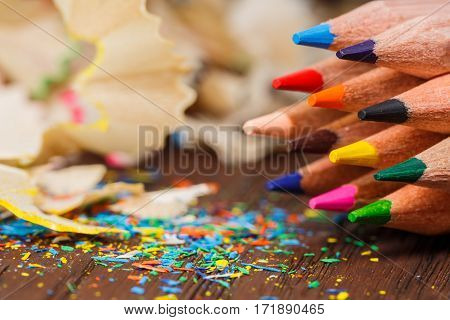 Wooden colorful pencils with sharpening shavings, on wooden table. Craetive idea, concept. Brown background. Blur. Education and school. Art and design. Painting and drawing.