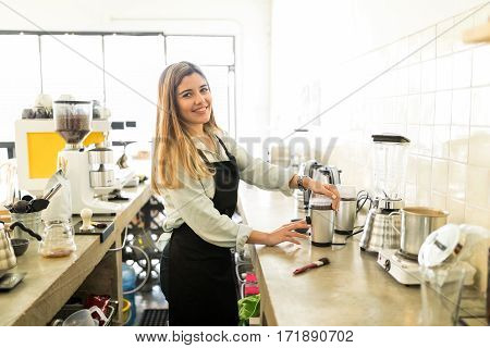 Cute Barista Grinding Coffee Grains