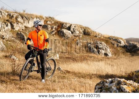 Cyclist standing on hill and watching the view. Beautiful landscape with rocks and sky. Cyclist in the orange jacket, helmet and glasses. Spring season in the countryside.