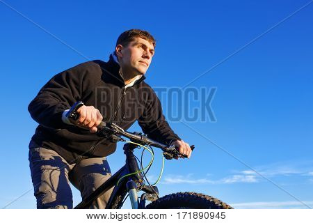 Mountain cyclist portrait, bicyclist in black jacket with mountain bike, blue sky on background, bottom view. Clouds. Detail of the bicycle. Hendlebar. Spring season in the countryside.