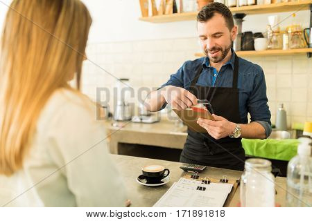 Barista Swiping Credit Card In A Coffee Shop