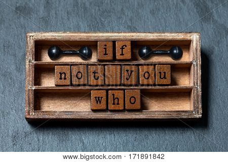 If not you who quote. Motivation and inspirational concept. Vintage box, wooden cubes with old style letters, ancient dumbbells. Gray stone textured background. Close-up, up view, soft focus.