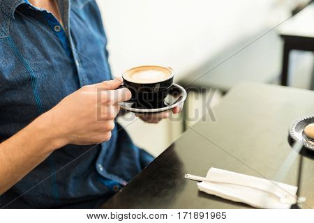 Man Enjoying A Cup Of Cappuccino