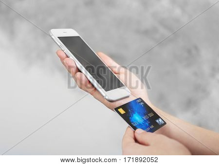 Woman holding credit card and using smart phone