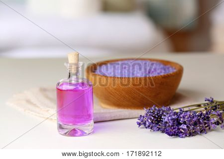 Bottle of essential oil with lavender and sea salt on background