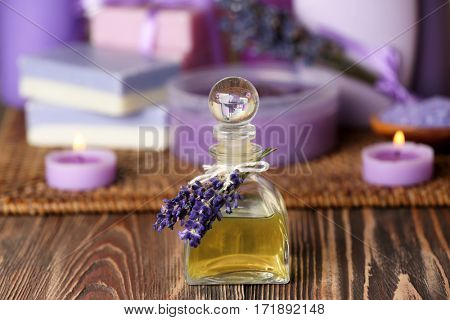 Bottle of lavender essential oil and body care products on background