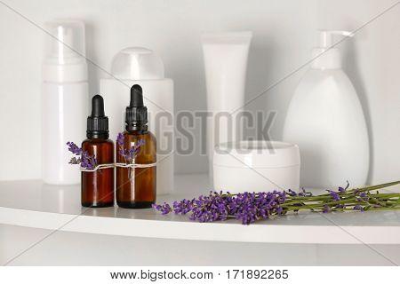 Bottles of essential oil with lavender on shelf in bathroom