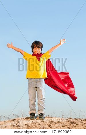 Boy playing superheroes on the sky background, teenage superhero in a red cloak on a hill