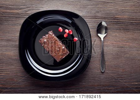 slice of brownie on a black plate on a wooden table with a spoon and pomegranate seeds