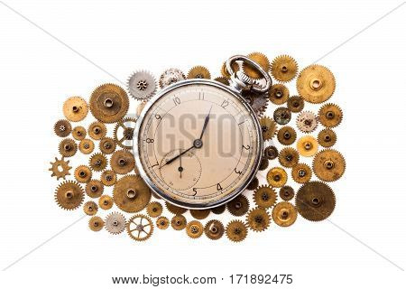 Vintage pocket watch and cogs gears wheels on white background. Vintage clockwork parts closeup. shallow depth of field