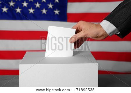 Male hand putting voting ballot into the box  on American flag background