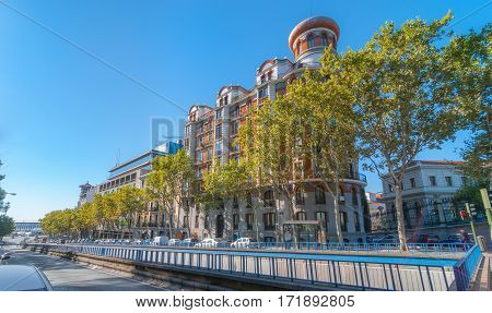 Streets scenes, Madrid.  View from Alfonso XII street where the tunnel begins.  Bright sun shines on tree lined street, European architecture shown in a corner block building featuring rounded end capped with eastern style dome.
