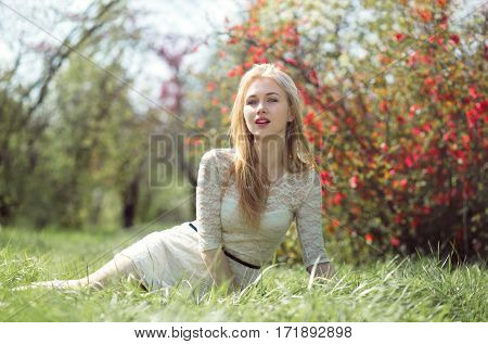 Lovely Blonde Sittting on The Grass Among Spring Flowers Garden.