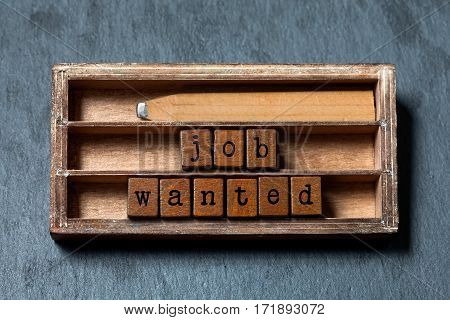 Job wanted phrase. Recruiting and work searching conceptual quote. Vintage box, wooden cubes with old style letters, wood pencil. Gray stone textured background. Close-up, up view, soft focus
