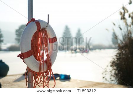 rescue ring with rope in front of a lake, winter, snow