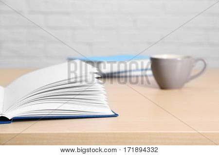 Opened book and cup of coffee on wooden table