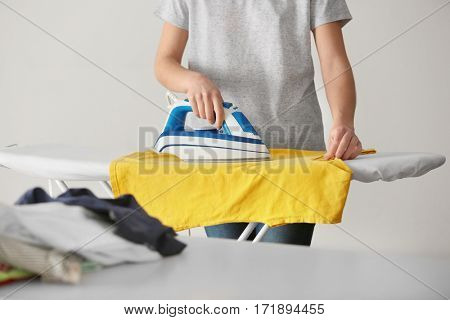 Woman ironing cloth on board
