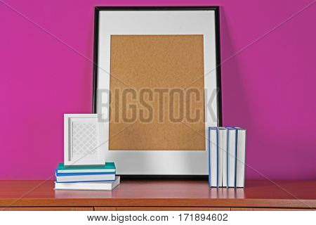 Books and frame on wooden table against pink background
