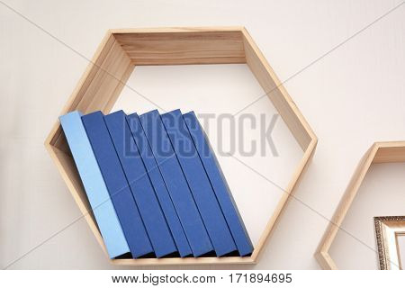 Set of books in row on wooden shelf against light wall