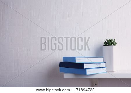 Stack of books on white wooden shelf