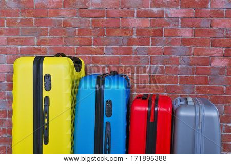 Color suitcases on brick background