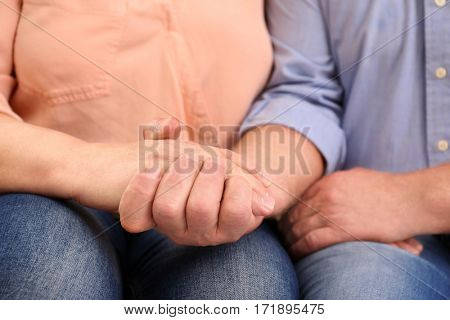 Closeup of husband holding wife's hand